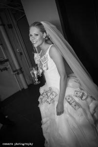 money pinning on bride's wedding dress